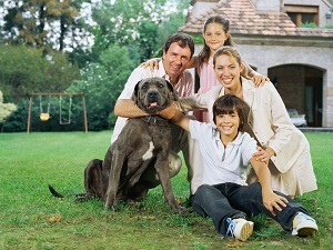 family with a dog sitting outside a home